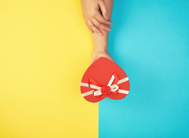 手はハートの形をした赤いボックスを閉じた紙を保持します。 Premium写真