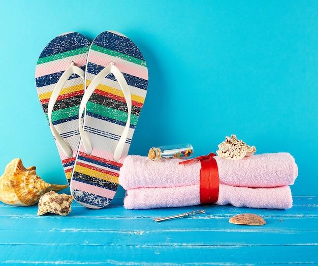 女性のビーチスリッパと青のピンクのタオルのペア Premium写真