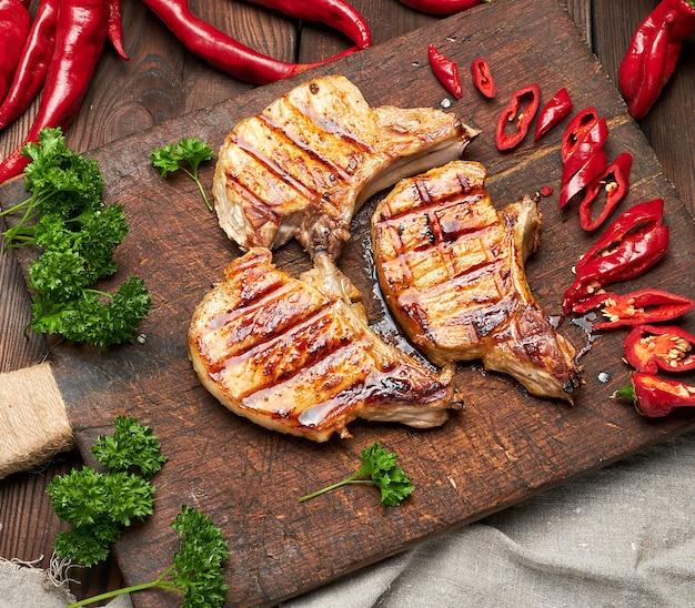 リブのポークフライステーキは、新鮮な赤唐辛子の横にあるヴィンテージの茶色の木の板の上にあり、上面図 Premium写真