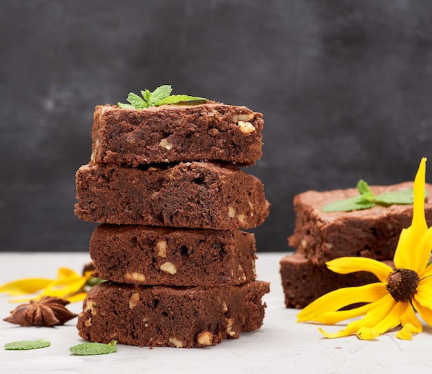 テーブルの上のクルミとブラウニーチョコレートケーキの正方形焼きたてのスタック Premium写真