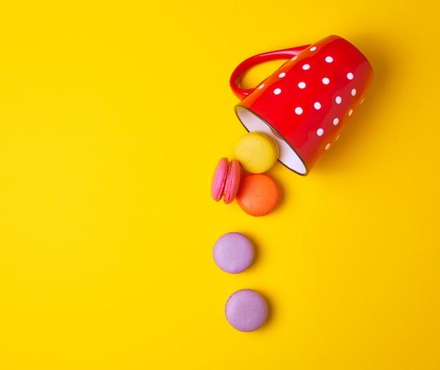 赤いセラミックカップから落ちてくる丸い色とりどりのマカロン Premium写真