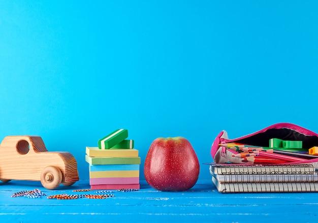 熟した赤いリンゴ、ノートブックのスタックとマルチカラーの木製鉛筆 Premium写真