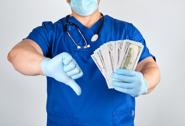 Доктор в синей форме и латексных перчатках держит в одной руке много денег, а в другой - плохой жест Premium Фотографии