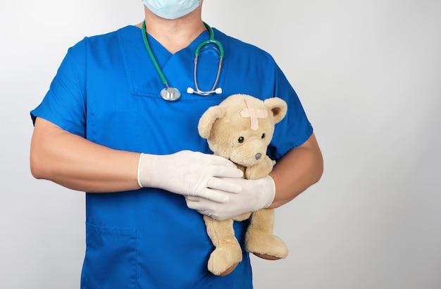 茶色のテディベアを保持している青い制服と白いラテックス手袋の医者 Premium写真