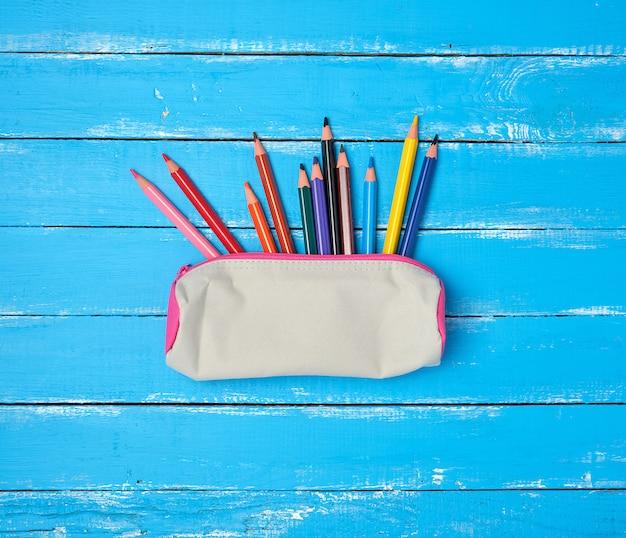 学校のグレーのテキスタイルペンケースと散らばった色とりどりの木製の鉛筆 Premium写真