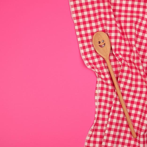 赤いキッチンタオルに刻まれた顔と木のスプーン Premium写真