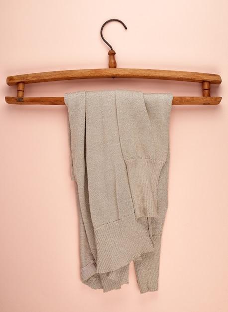 Бежевый женский свитер висит на старинной деревянной вешалке Premium Фотографии