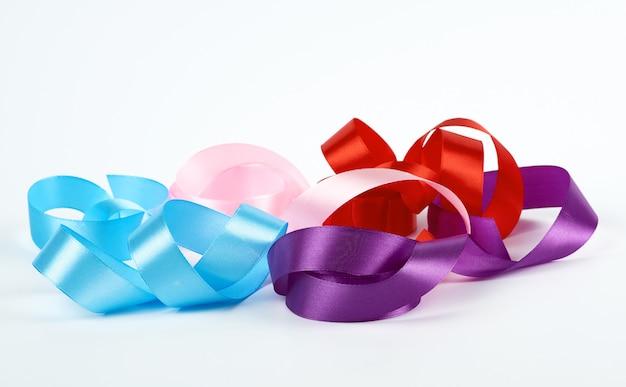 Синие, розовые, красные и фиолетовые крученые атласные ленты на белом Premium Фотографии