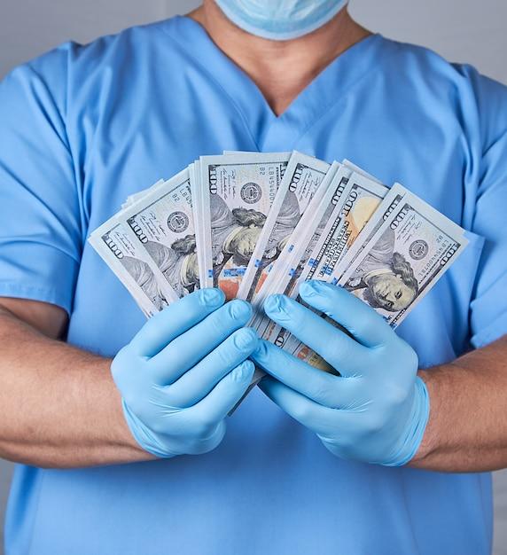 Доктор в синей форме и латексных стерильных перчатках держит много бумажных денег Premium Фотографии