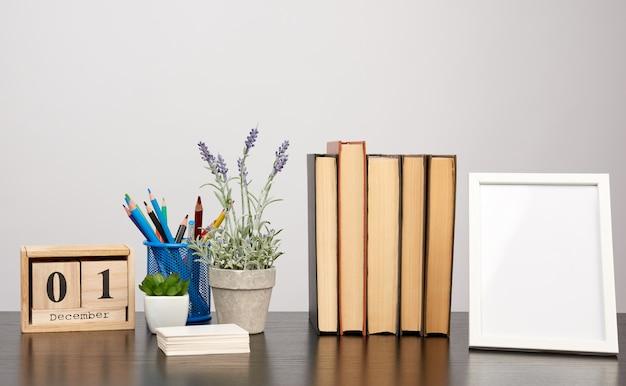 空の白いフォトフレーム、書籍のスタック、黒いテーブルにラベンダーの成長の鍋 Premium写真