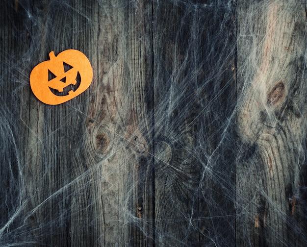 白いクモの巣と刻まれたカボチャの形をしたフェルトの装飾 Premium写真