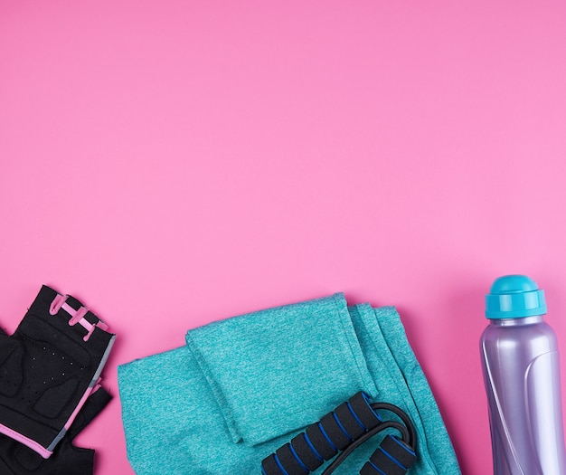 Розовые женские кроссовки, бутылка воды, перчатки и скакалка для занятий спортом на розовой поверхности Premium Фотографии