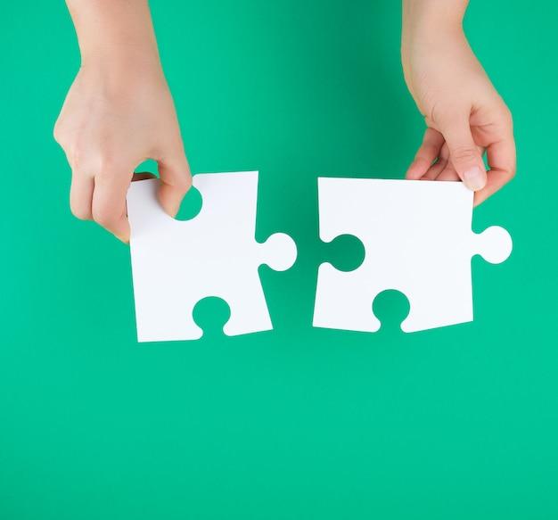 Белые большие пазлы в женской руке на зеленом фоне Premium Фотографии