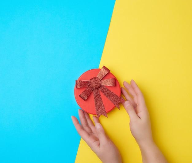 手は赤い弓で閉じた段ボール箱を保持します Premium写真