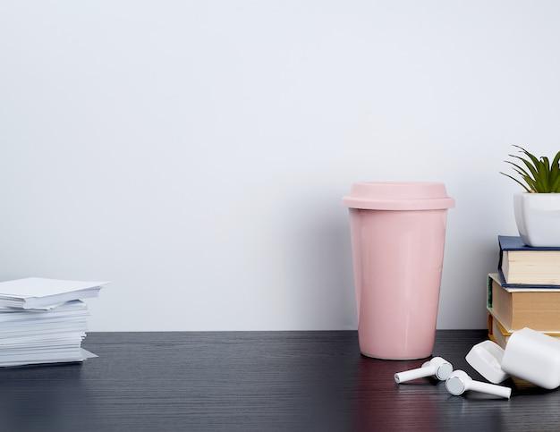 Беспроводные белые наушники с зарядкой, розовая керамическая чашка с кофе и книгами Premium Фотографии