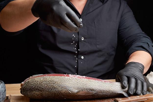 Шеф-повар в черной рубашке и черных латексных перчатках готовит филе лосося на деревянной разделочной доске Premium Фотографии