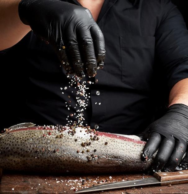 黒のシャツと黒のラテックス手袋のシェフが木製のまな板にサーモンの切り身を準備します。 Premium写真