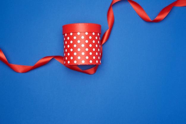 白い水玉と赤い絹のリボンで閉じた段ボールの赤いボックス Premium写真