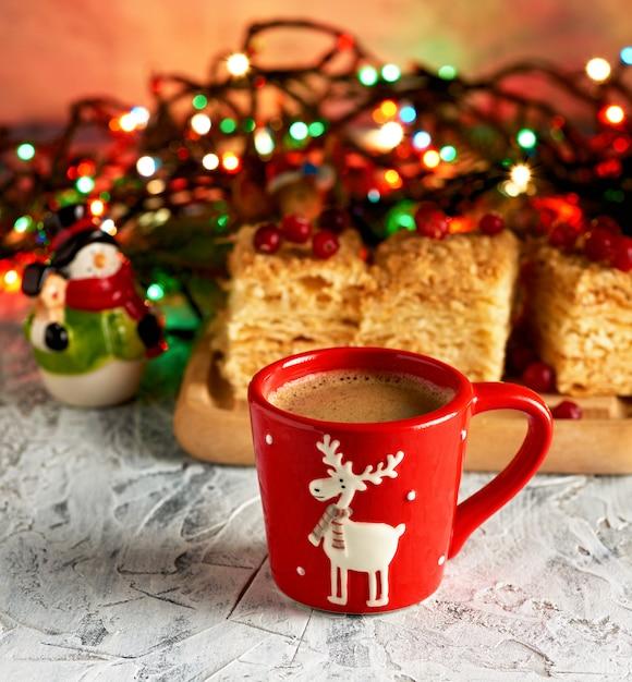 Красная керамическая чашка с черным кофе возле зеленых веток еловых и новогодних игрушек Premium Фотографии