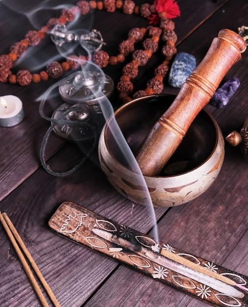 銅の歌ボウルと茶色のテーブルの上の木の棒 Premium写真