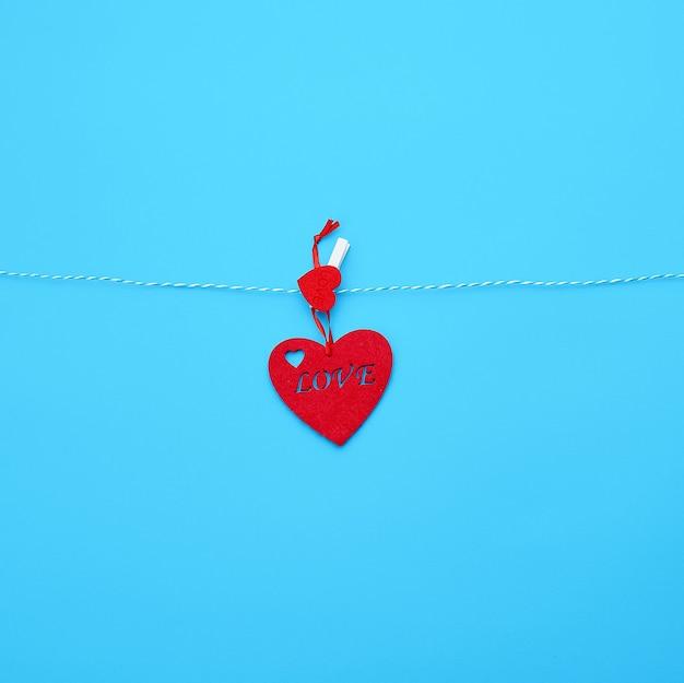 白いロープにぶら下がっていて洗濯はさみで留められた赤いフェルト Premium写真