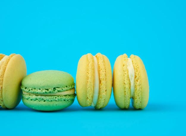 黄色と緑の丸いアーモンド小麦粉ケーキクリームとマカロン Premium写真