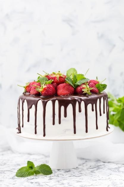 Торт с белыми сливками, шоколадным топингом и клубникой. Premium Фотографии