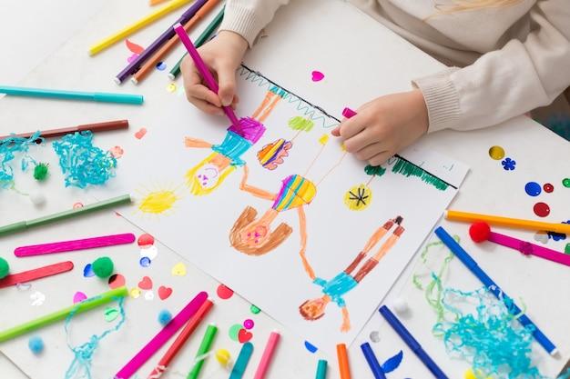 子供はマーカーで友人を描きます Premium写真
