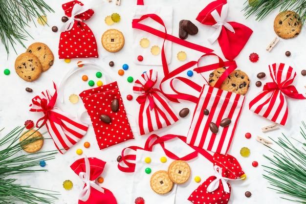 子供向けのキャンディーとクッキーを使用したアドベントカレンダーの準備プロセス。お菓子とギフトのクリスマス Premium写真