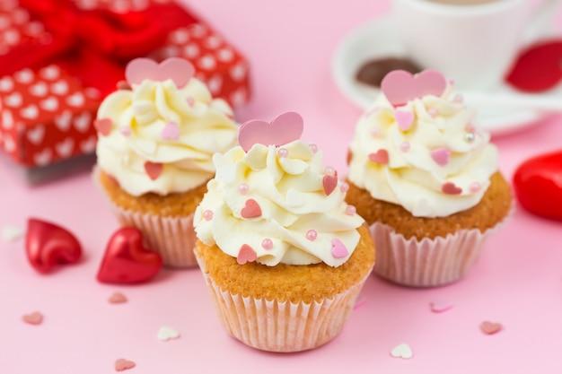 バレンタインデーのお菓子、ピンクのハートが飾られたカップケーキ Premium写真