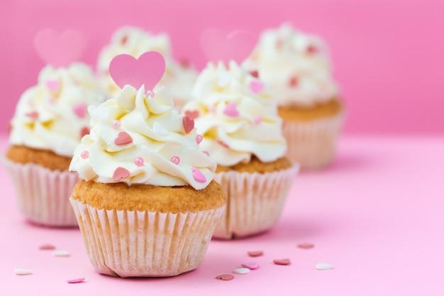 バレンタインデーのお菓子。ピンクの背景にカップケーキの装飾が施された心 Premium写真