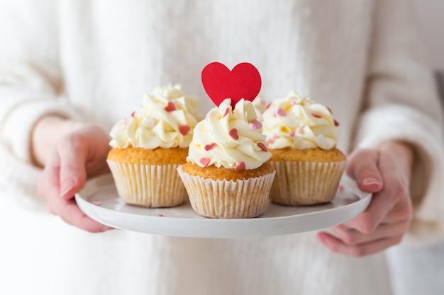 バレンタイン・デー。甘い贈り物。心で飾られたカップケーキとプレートを保持している女性の手 Premium写真