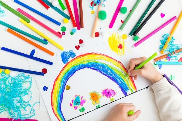 子供がマーカーで虹を描く Premium写真