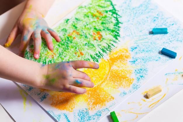 赤ちゃんはクレヨンを描きます。子供の創造性幼児の発達 Premium写真