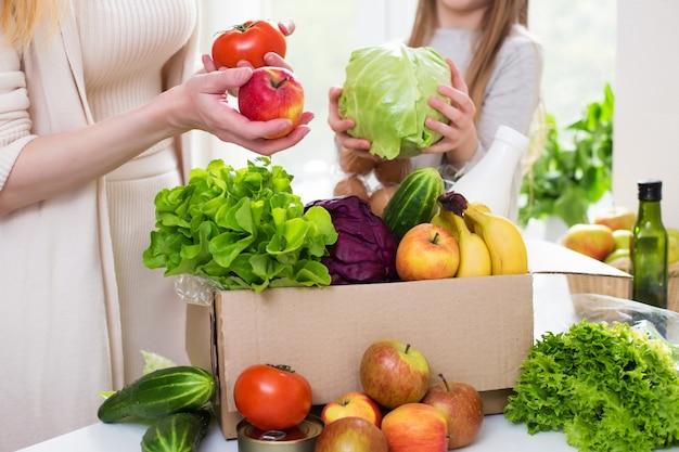 Доставка еды. мама и дочка распаковывают коробку с овощами и фруктами. онлайн заказ из продуктового магазина Premium Фотографии