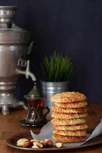 木製のテーブルのサモワールでナッツと紅茶とオートミールクッキーを杭します。 Premium写真