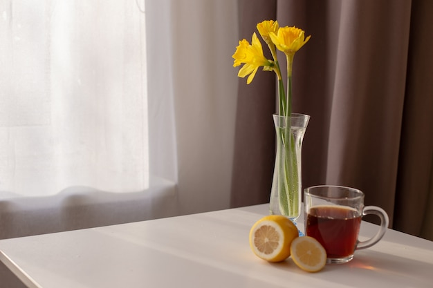 白と茶色のカーテンが付いた窓際のテーブルは、ガラスの花瓶に入ったお茶、レモン、黄色の水仙です。 Premium写真