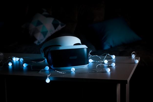 仮想現実のヘルメット。ゲームの新しい経験。素晴らしい感情、クールな休息。仮想現実の眼鏡はネオンの光の中にあります。 Premium写真