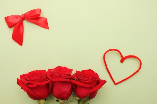 Три красные розы с каплями воды на них Premium Фотографии