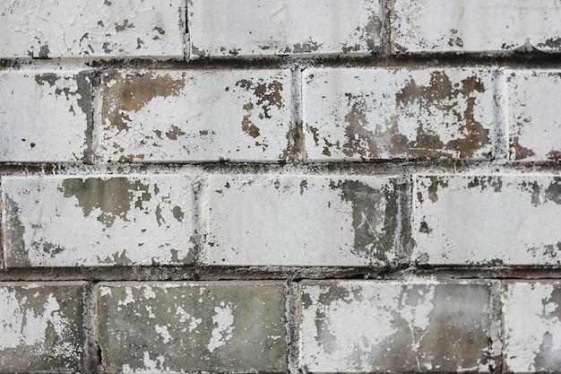 使い古されたパターンと古い塗料の痕跡でレンガの壁 Premium写真