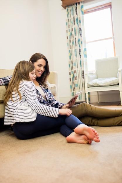 Мать и дочь, используя цифровой планшет в гостиной Бесплатные Фотографии