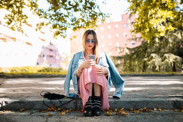 Задумчивый молодая женщина с очками, сидя на тротуаре, глядя на мобильный телефон, ожидая кого-то в парке. человеческие эмоции, выражение лица, чувства, реакция языка тела. эмоциональная концепция. Premium Фотографии