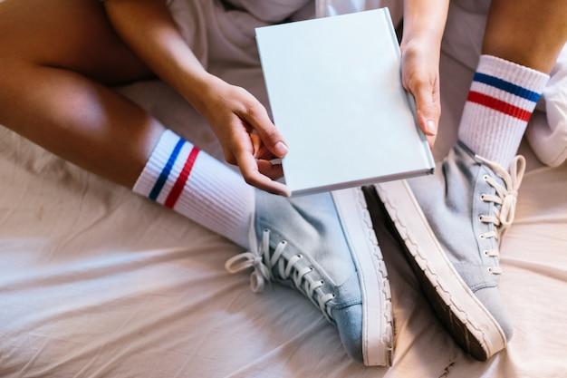 本を読み始める自宅で青いスリッパとベッドの中で女性 Premium写真