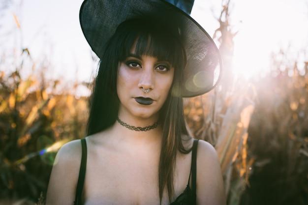 日没時のトウモロコシ畑でハロウィーンコスチューム魔女少女の肖像画。長い黒髪と黒い唇の魔女帽子で美しい深刻な若い女性 Premium写真