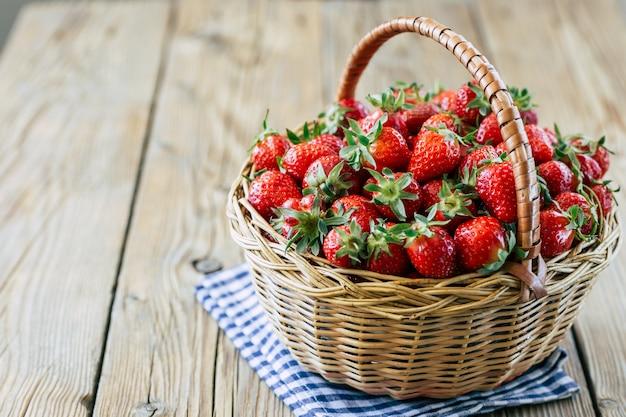 木製の背景上のバスケットに新鮮な熟したイチゴ Premium写真