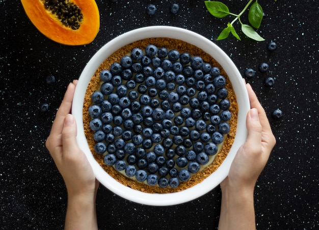女性の手でブルーベリーのチーズケーキ Premium写真
