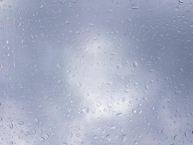 窓からすの背景に多くの雨滴 Premium写真