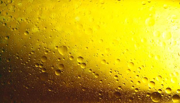 黄色の抽象的な背景に均等に配置された水の泡。 Premium写真