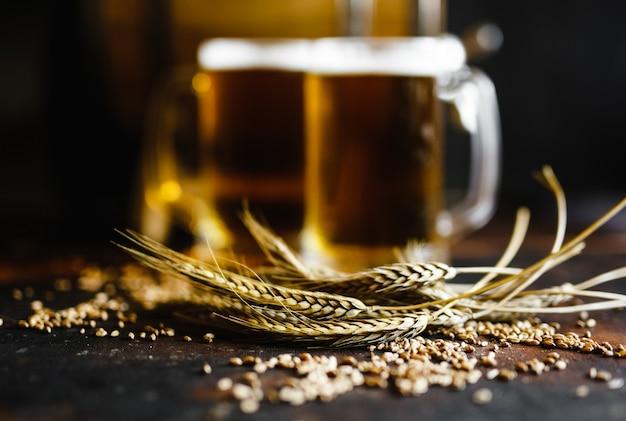 古い木製のテーブルにビールと小麦のスパイス Premium写真