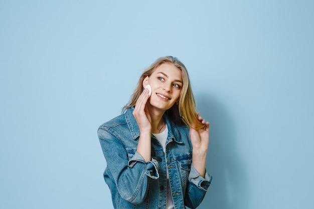 Красивый женский портрет с помощью ватного тампона и думает о чем-то на синем фоне Premium Фотографии
